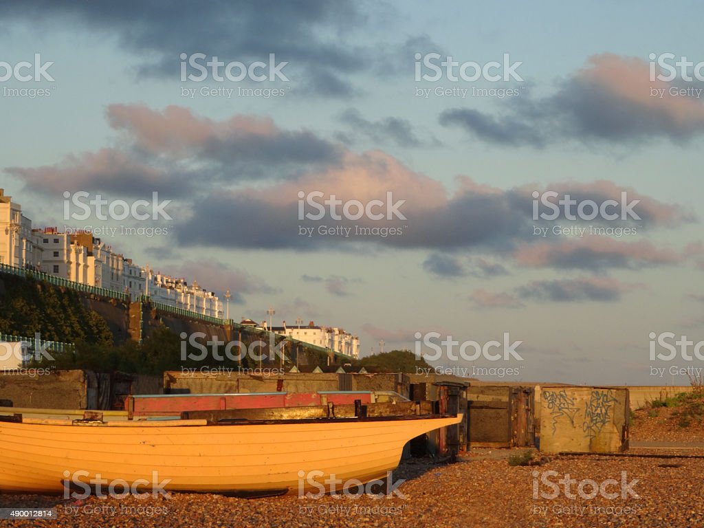 Image of sunset on Brighton beach with boats, houses, graffiti stock photo