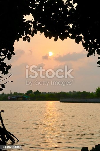 View of sunset in the Kerala Backwaters, India as seen from the prow of a wooden canoe through a frame of  mangrove trees.