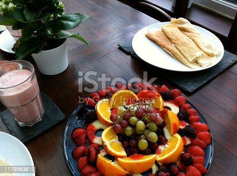 Stock photo showing a fruit platter of red and green grapes, orange quarters, apple rings and sliced strawberries ready to be added to a breakfast of pancakes layed out on a dark wood table in a conservatory.