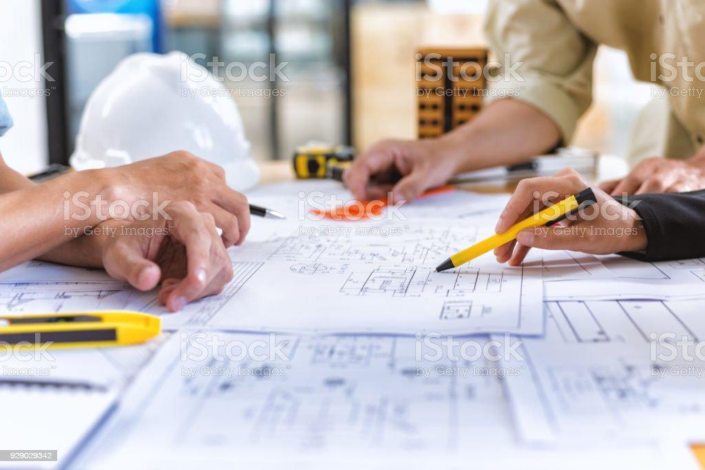 팀 엔지니어의 이미지 엔지니어링 도구 사무실에서 책상에 새로운 프로젝트에 건설 청사진을 확인합니다. - 로열티 프리 가리키기 스톡 사진
