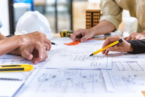 팀 엔지니어의 이미지 엔지니어링 도구 사무실에서 책상에 새로운 프로젝트에 건설 청사진을 확인합니다 가리키기에 대한 스톡 사진 및 기타 이미지