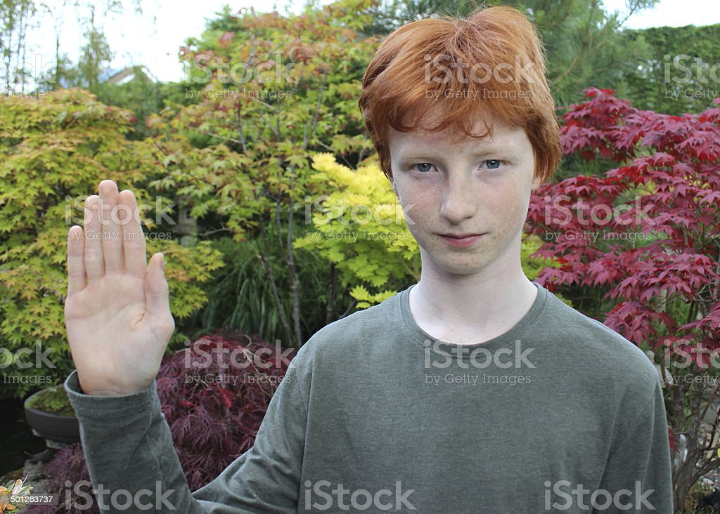 Image of teenage boy hoding up hand to say 'stop' stock photo