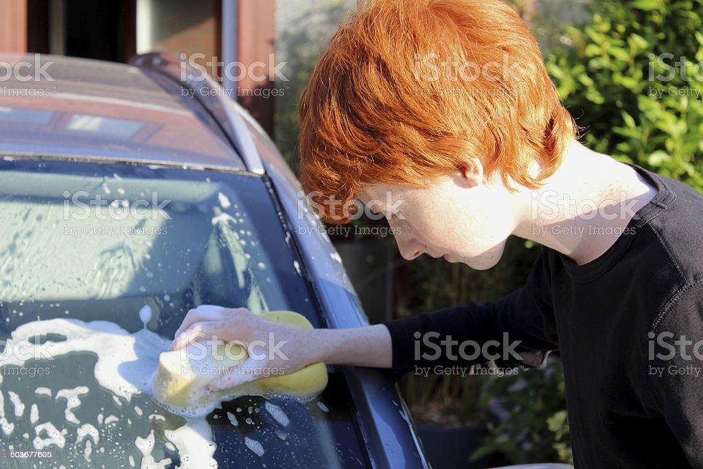 Image of teenage boy washing car windscreen with sponge / car-wash royalty-free stock photo