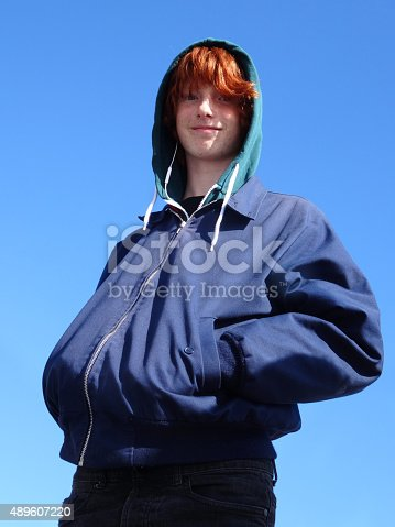 Photo showing a teenage boy with his red hair being visible beneath a green hoodie.  He is wearing a blue jacket and is pictured against the sky, smiling at the camera.