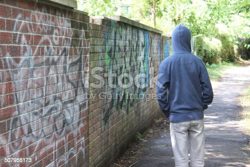 Photo showing a teenage boy / youth wearing a blue hoodie and standing beside a brick wall in an overgrown alleyway, in a run-down part of the city.