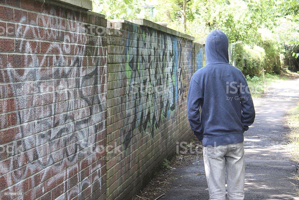 Image of teenage boy / youth wearing hoodie, beside graffiti wall stock photo