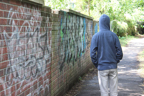 Image of teenage boy / youth wearing hoodie, beside graffiti wall stock photo
