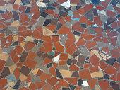 Image of terracotta mosaic tiled pattern floor with broken tiles