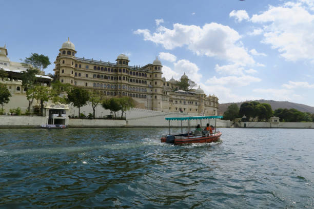 Image of the City Palace complex viewed from a tourboat on Lake Pichola, Udaipur, Rajasthan, India Stock photo taken from tourism cruise boat across Lake Pichola with views of the City Palace, Udaipur, Rajasthan, India. lake pichola stock pictures, royalty-free photos & images