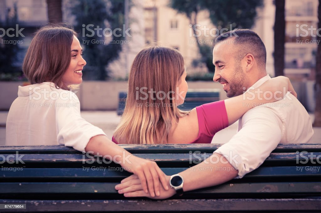 Image of the love triangle between young people outdoor. stock photo