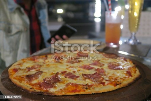 Stock photo of thin and crispy pancetta ham pizza with golden melted mozarella cheese at Italian restaurant with al fresco dining outside in bar garden, photo at night with hungry diner man drinking beer / cocktails holding mobile and eating delicious pizza.