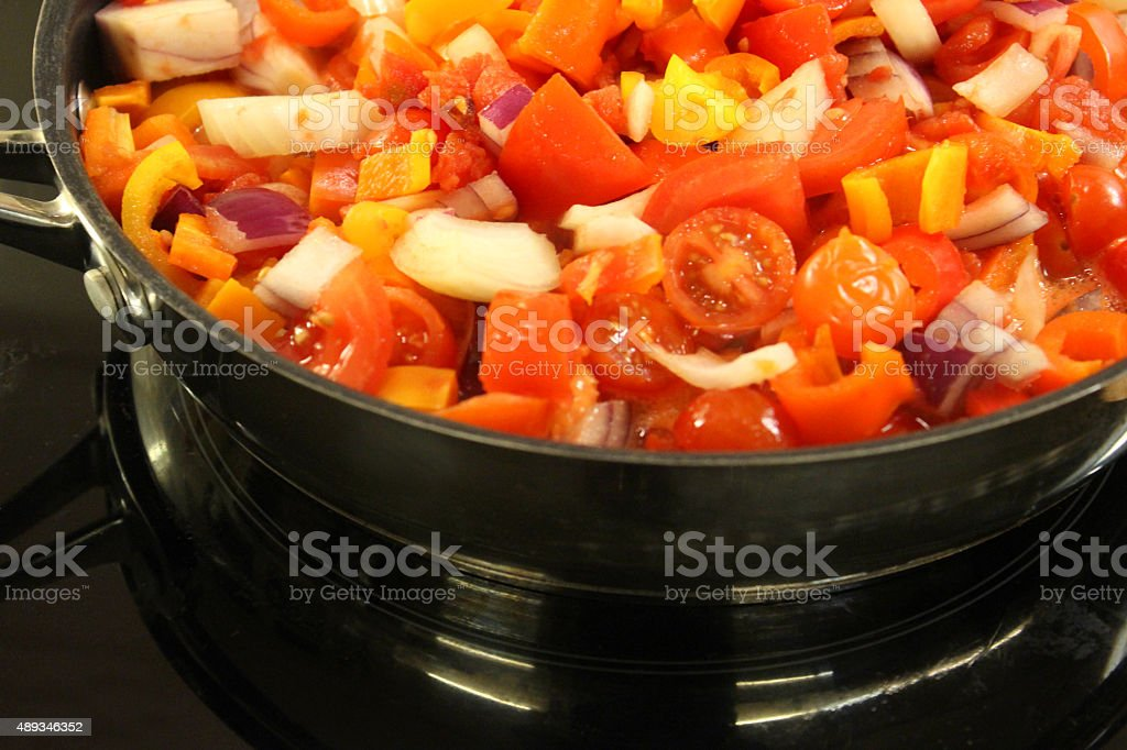 Image of tomatoes, onions and peppers, vegetables cooking in frying-pan stock photo