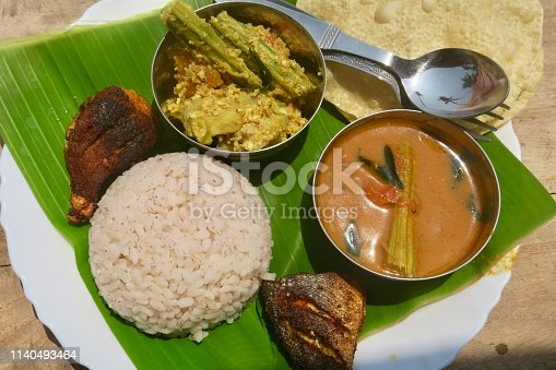 Photo showing traditional kerela, South Indian local food served on a green banana leaf as lunch or dinner. The food consists of papad / papadum / poppadom, fried king fish and spiced barbecued tuna steak, aviyal, alleppey coconut mango fish curry, matta / rosematta / Palakkadan with wild Keralan red rice mounded using an upside down bowl as a mould.