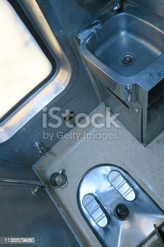 Stainless steel, squat toilet facilities aboard an Indian train.