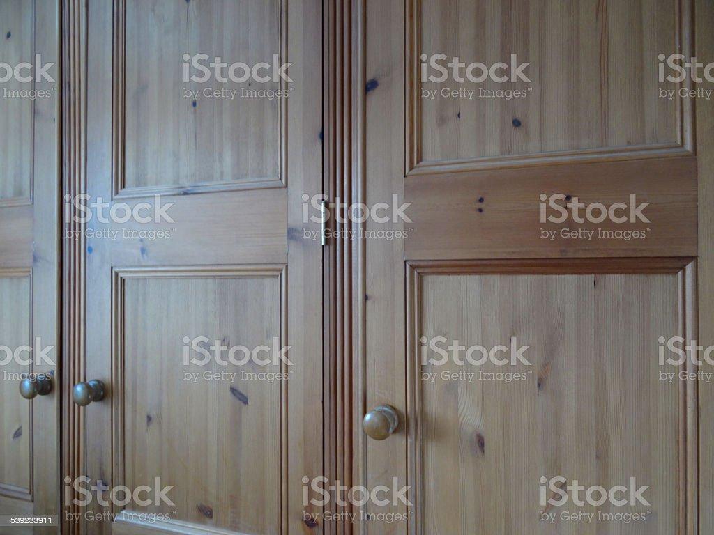 Image of triple wooden pine wardrobe doors in bedroom, waxed royalty-free stock photo