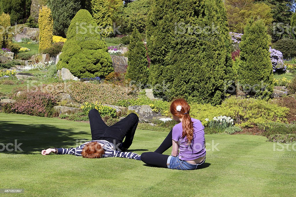 Image Of Two Children Relaxing On Sunny Lawn In Garden Stock Photo