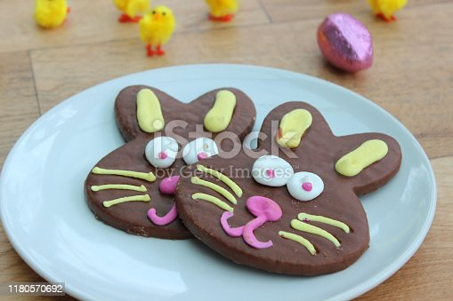 Photo showing Easter bunny shaped biscuits covered in chocolate and served on a plate surrounded by fluffy yellow chicks.