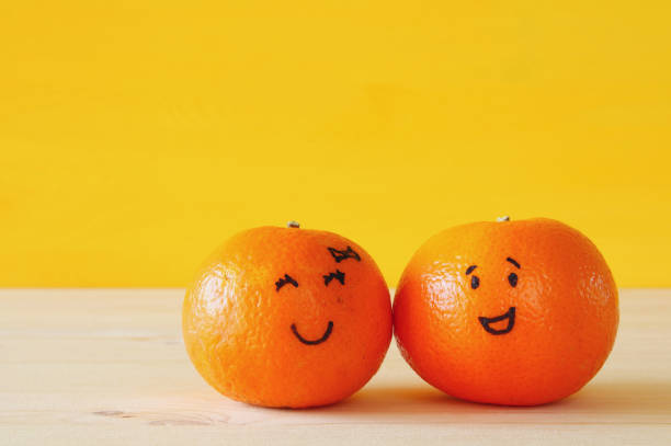 Image of two clementines with drawn smiley faces - Photo