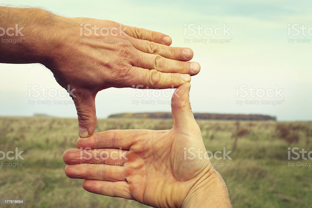 Image of two hands framing landscape composition stock photo