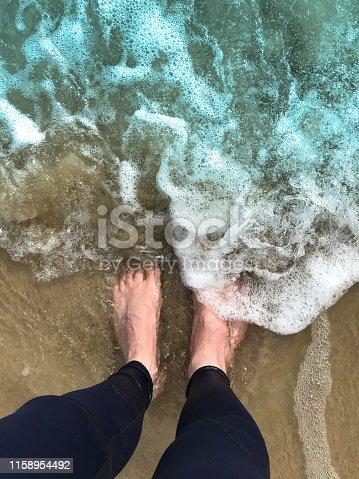 174919648 istock photo Image of two white feet on sand with English man getting wet dark blue men's leggings meggings / sportswear jogging pants, paddling / standing footprints in sea water spray washing golden sandy beach away, barefoot in sea seaside waves sinking in wet sand 1158954492