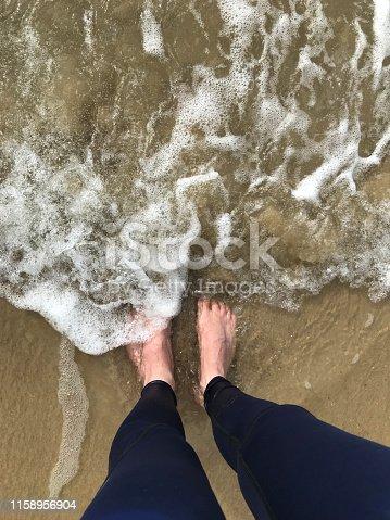 174919648 istock photo Image of two white feet on sand with English man getting wet dark blue men's leggings meggings / sportswear jogging pants, paddling / standing footprints in sea water spray washing golden sandy beach away, barefoot in sea seaside waves sinking in wet sand 1158956904