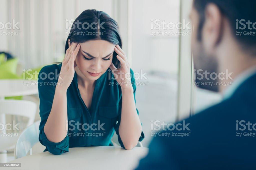 Image of two workers at a meeting in a restaurant. Young pretty exhausted businesswoman having headache because of problems at work stock photo