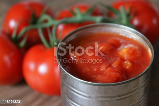 Stock Photo of unbranded generic tin of chopped tomatoes pieces / canned passata from supermarket with large vine tomato plant on wooden chopping board / bread board, diced and chopped Italian tinned tomatoes puree juice, peeled for ragu pasta sauce with garlic