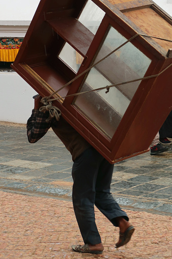 Image of unrecognisable asian man bent over transporting wooden cabinet on back, furniture tied to back with rope, furniture removal