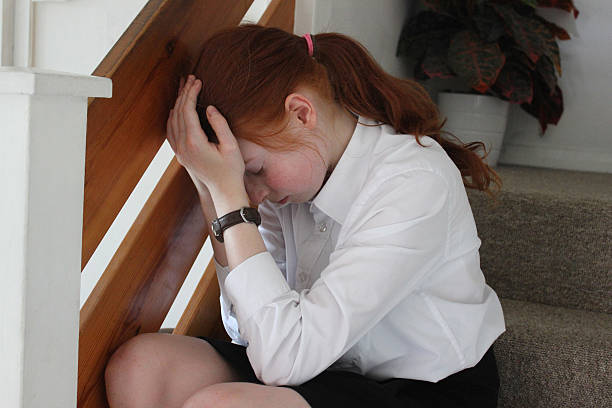 Image of upset girl crying on stairs, head in hands stock photo