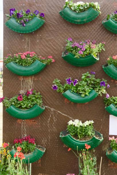 Image of vertical wall garden using recycled rubber car tyre sections as plant pots, upcycled tubes filled with soil and plants, painted green and assembled in column design, environmental conservation and space saving garden design concept stock photo
