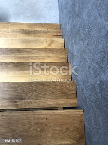 Stock photo looking down at a tiled marble effect floor from a step on a modern, wooden staircase.