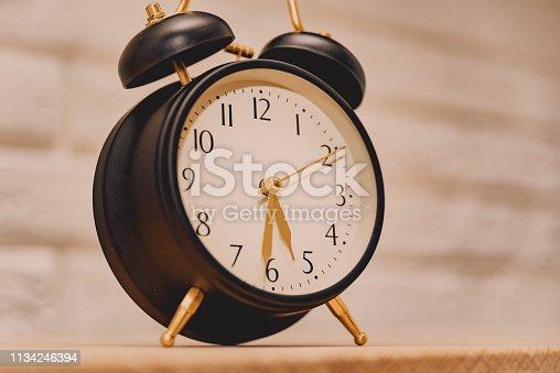 A vintage, black alarm clock showing different time,  defocused background.