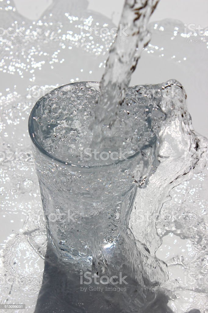 Image of water being poured into diner glass, splashing, sparkling stock photo