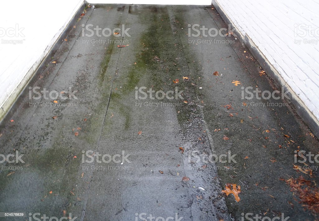 Image of wet felt / asphalt flat roof in rain, puddles stock photo