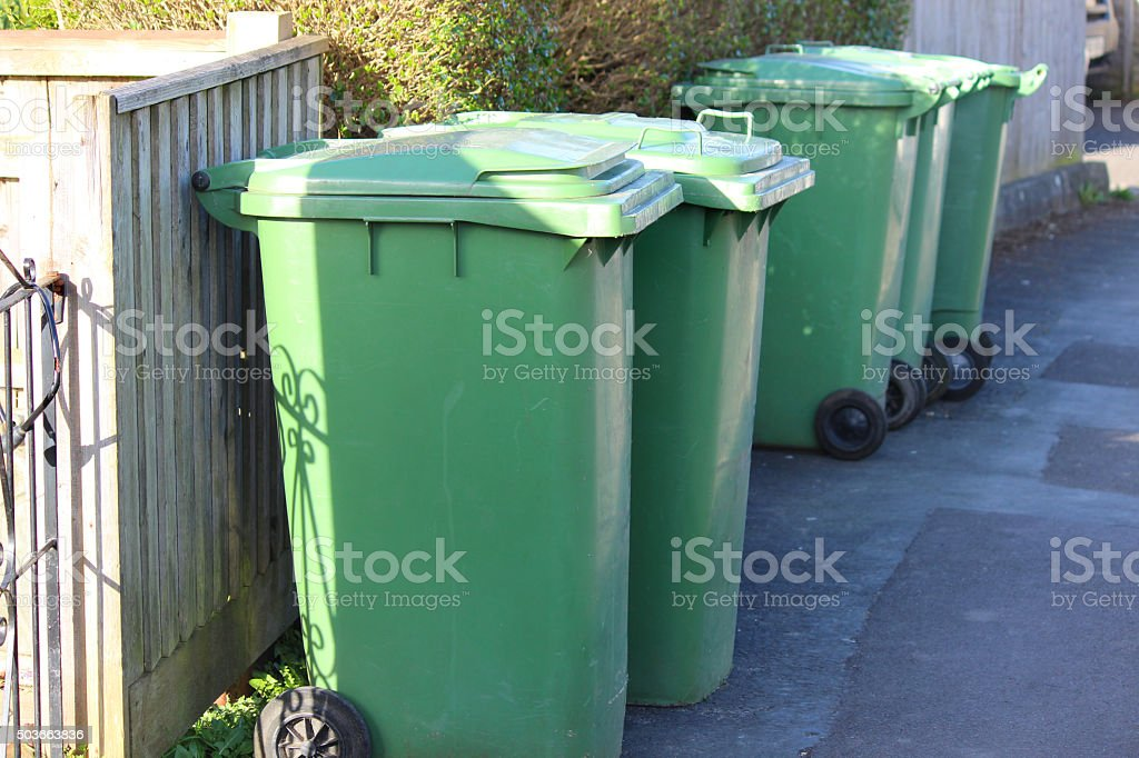 Image of wheelie-bins / dustbins in row, waiting for refuse collection stock photo
