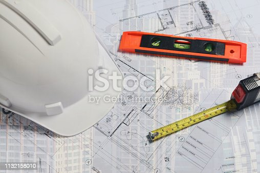 istock image of white construction helmet with measuring level and site plan 1132158010