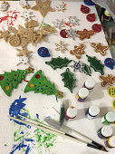 Image of winter Christmas crafting session making Xmas tree decorations of trees, holly leaves, snowflakes, gingerbread men / man, stars, baubles and snowmen, from baked salt dough cookies cut from cookie cutters being painted with poster paint brushes