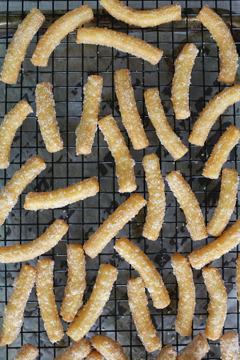 Stock photo showing elevated view of a batch of freshly, cooked churros, a fried-dough pastry sprinkled with sugar left on a metal, wire cooling rack on a grey tongue and groove effect background. These are a popular snack or breakfast with a hot chocolate drink.