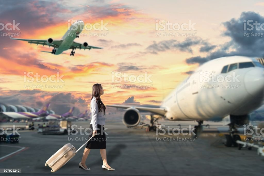Image of woman in airport looking at taking off airplane, business stock photo