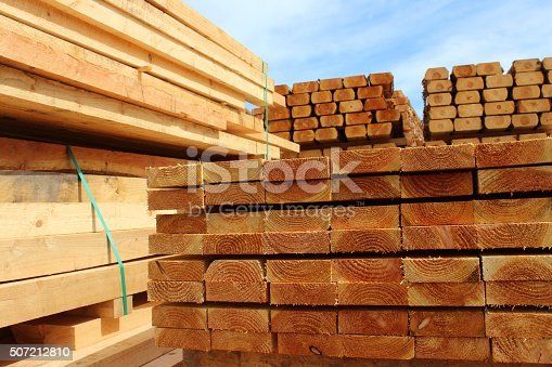 Photo showing some huge piles of wooden planks and fence posts, freshly sawn up in a sawmill and piled in the timber yard, ready to be sold to the general public.
