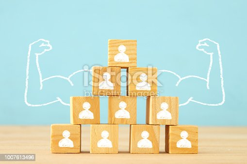 istock image of wooden blocks with people icons over table ,building a strong team, human resources and management concept. 1007613496