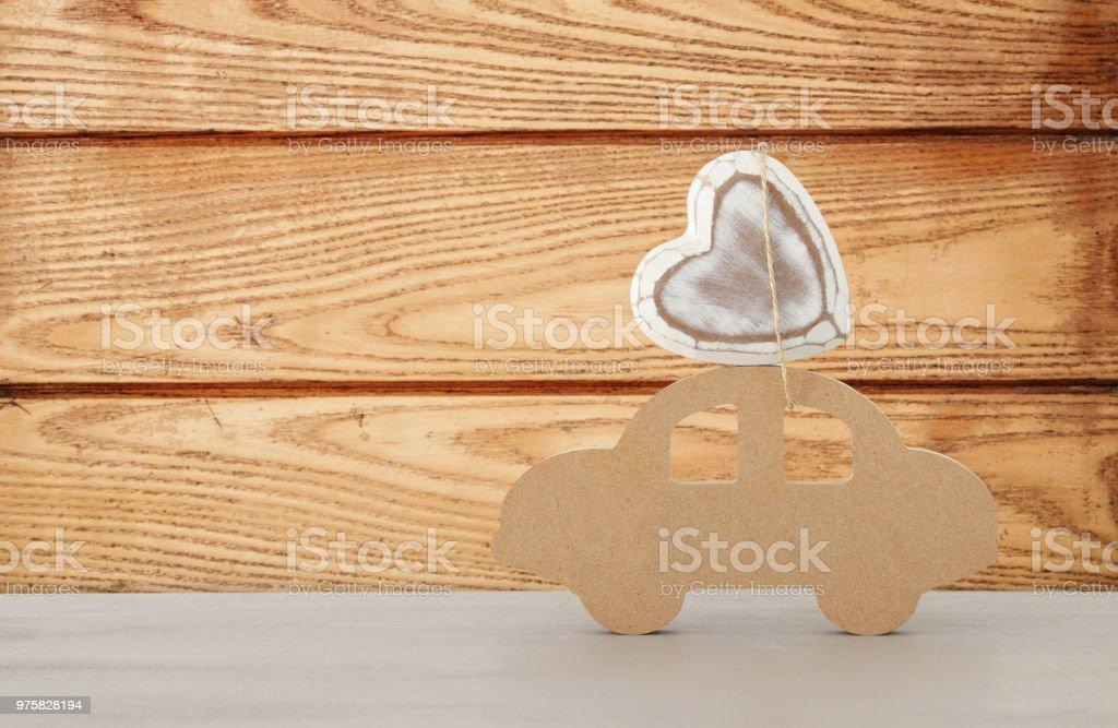 Bild des hölzernen Auto mit Herzen auf dem Dach, Geschenk für Papa. Vatertag-Konzept. - Lizenzfrei Abenteuer Stock-Foto
