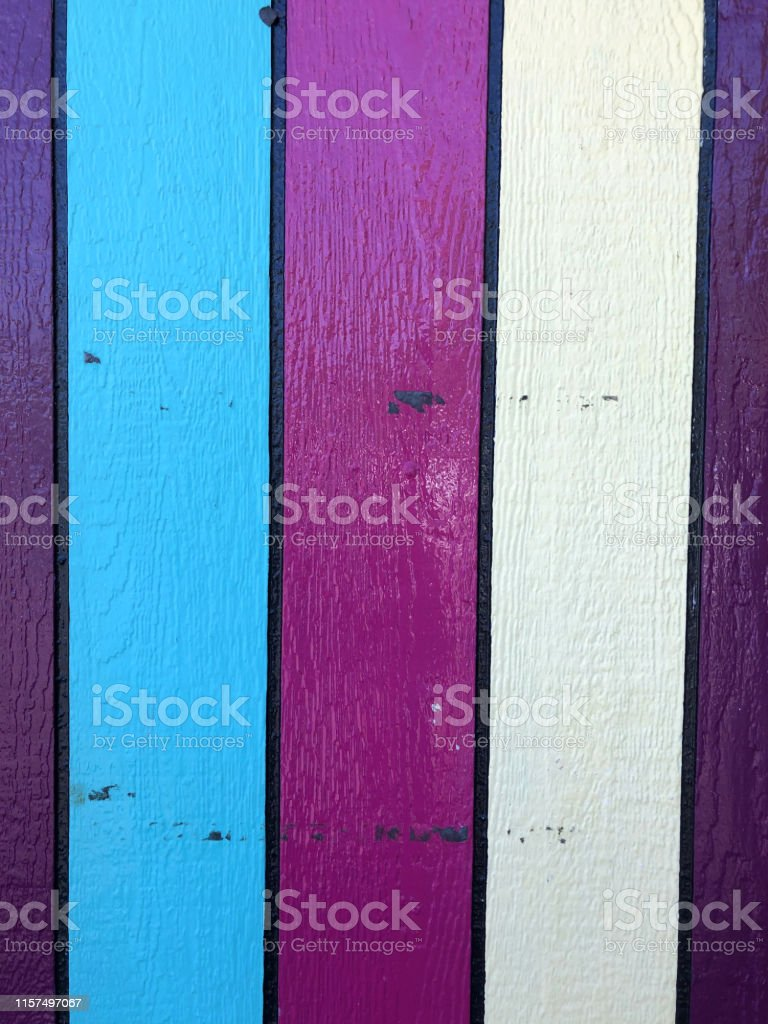 Stock photo of wooden fence painted in rainbow colours on timber wood...