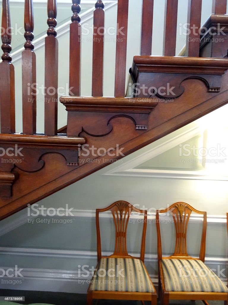 Image of wooden stair bannisters / spindles, staircase, antique chairs striped-cushions stock photo