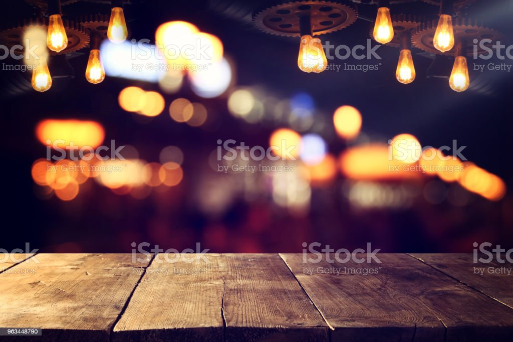 Image of wooden table in front of abstract blurred restaurant lights background. - Zbiór zdjęć royalty-free (Bez ludzi)