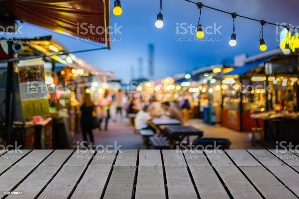 Image of wooden table in front of decorative outdoor string lights bulb in night market with blur people, Festival and holiday concepts, can used for display or montage your products. stock photo