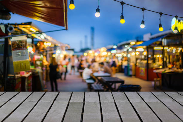 Image of wooden table in front of decorative outdoor string lights bulb in night market with blur people, Festival and holiday concepts, can used for display or montage your products. Image of wooden table in front of decorative outdoor string lights bulb in night market with blur people, Festival and holiday concepts, can used for display or montage your products. night market stock pictures, royalty-free photos & images