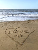 Image of writing drawn on sunny beach with Love me words written inside drawn heart in sand with stick, by sea waves, concept social media photo of handwriting letters in soft golden sand on Bournemouth beach, Dorset, England seaside coastline view