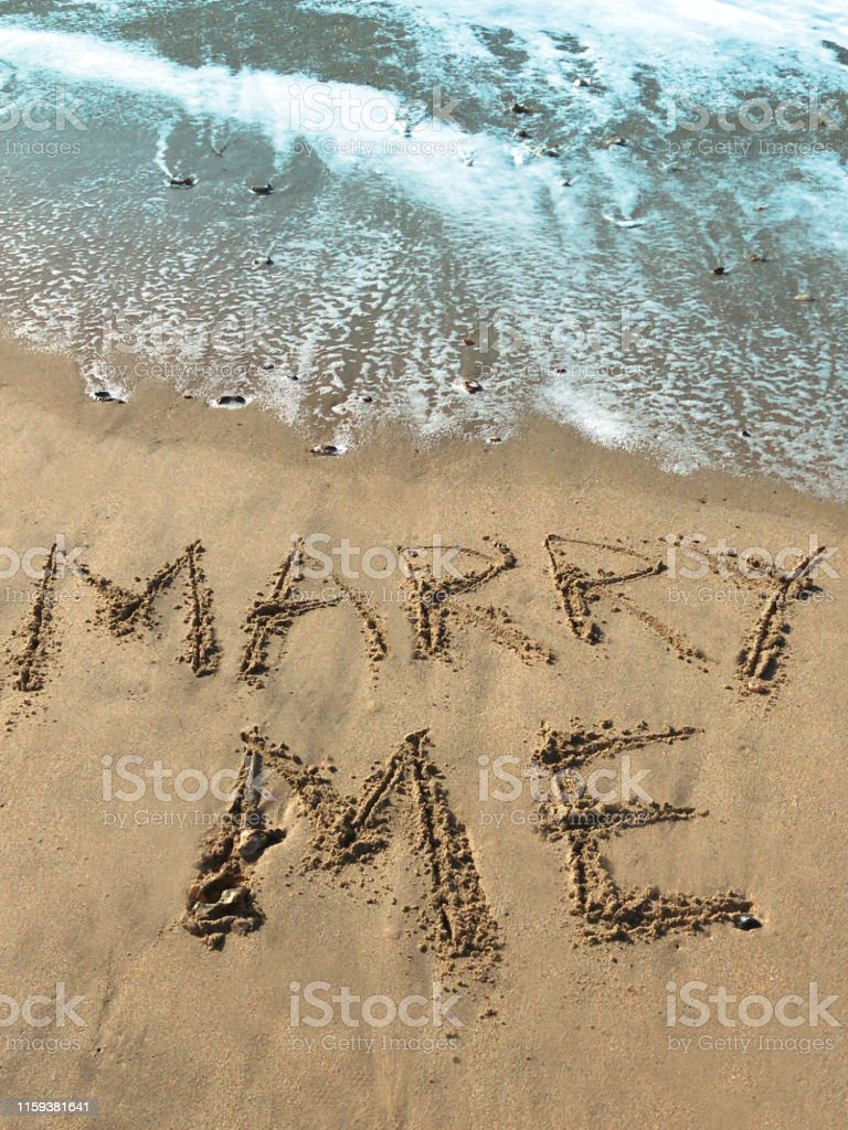 Stock photo of writing drawn on sunny beach with Marry me words...