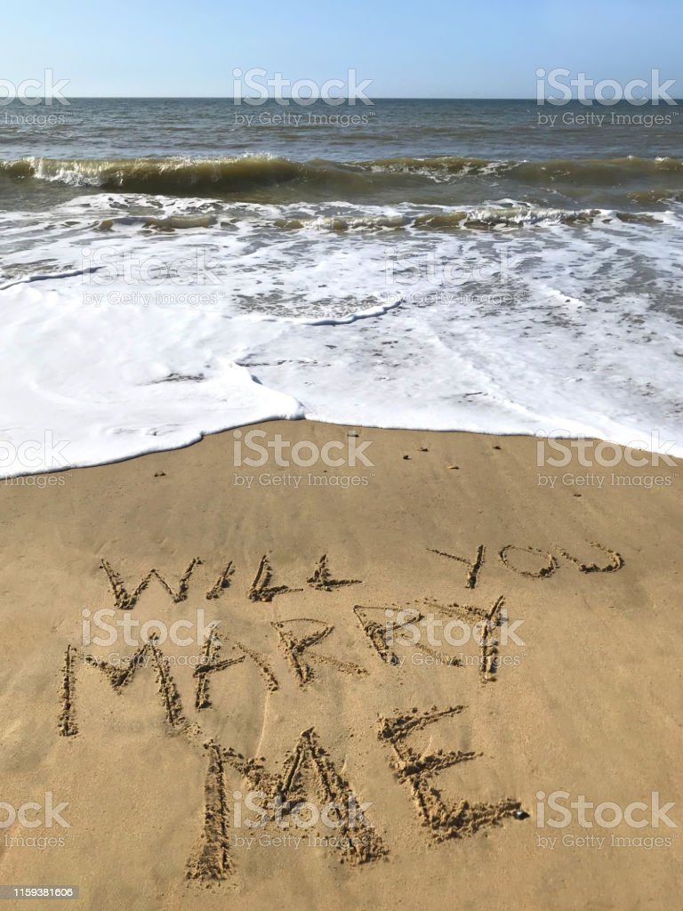 Stock photo of writing drawn on sunny beach with Will you marry me...